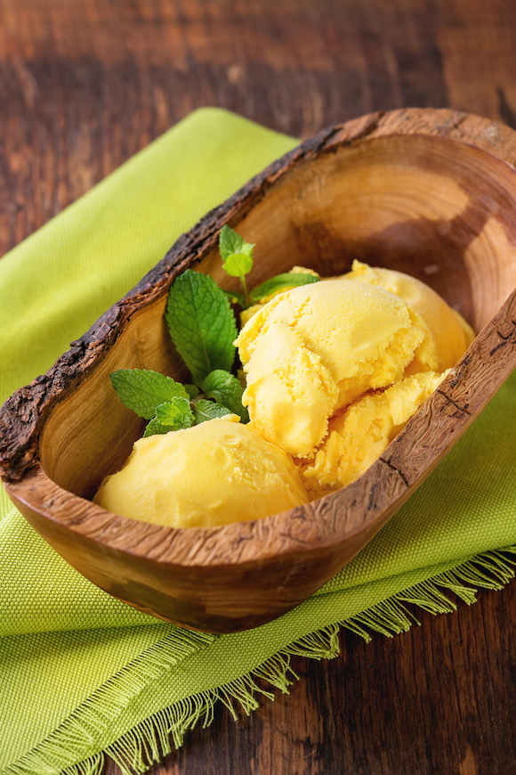 Homemade mango ice cream with fresh mint in olive wood bowl, served on green textile napkin over wooden textured background.